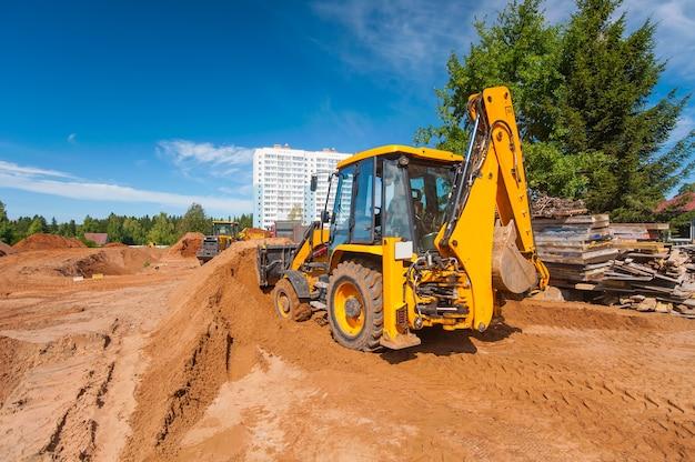Żółty traktor wyrównuje ziemię na placu budowy latem