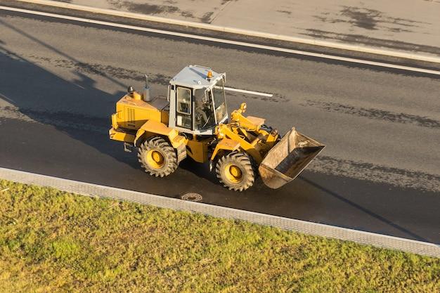 Żółty traktor z łyżką na autostradzie.