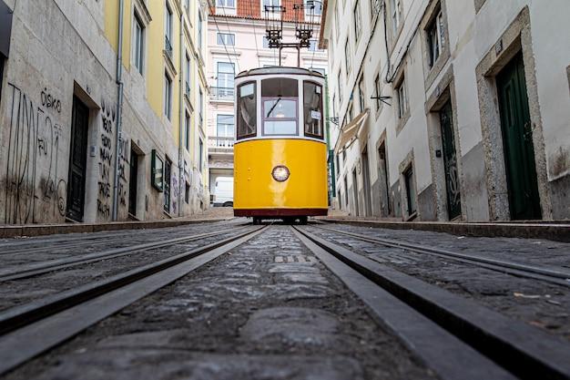 Żółty tramwaj jadący wąską uliczką otoczoną starymi budynkami