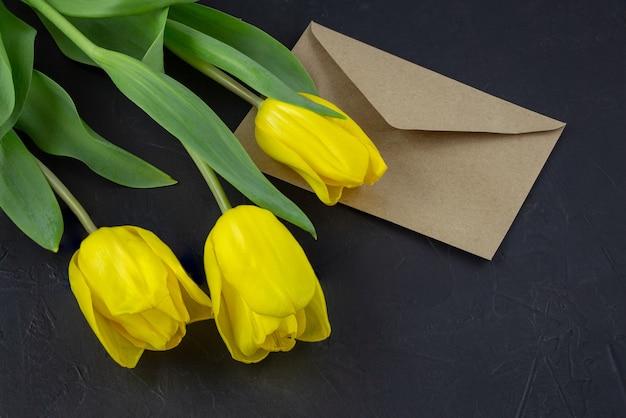Żółty tulipan w pobliżu pustej kartki z życzeniami i kopert na czarnym tle z miejscem na tekst