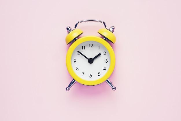Żółty vintage budzik na różowo. koncepcja czasu letniego. leżał z płaskim, skopiuj miejsce na tekst.