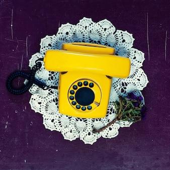 Żółty vintage telefon stary drewniany tło