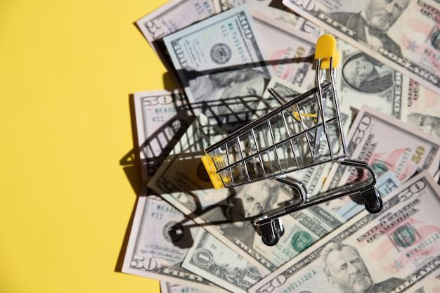 Żółty wózek na zakupy i dolarowi rachunki na żółtym tła zakończeniu. pojęcie finansów, zakupy online, wysokie koszty leków. koncepcja marketingu online lub budżetowania zakupów