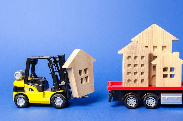 Żółty wózek widłowy ładuje drewnianą figurę domu do koncepcji transportu ciężarówki