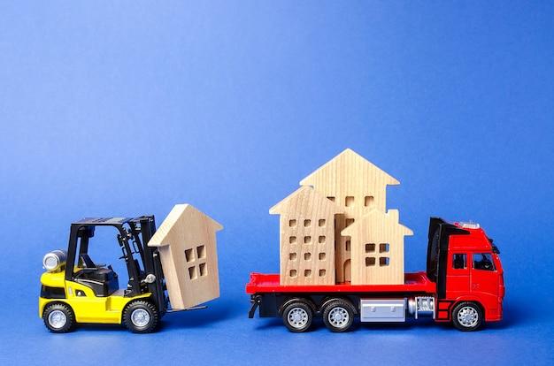 Żółty wózek widłowy ładuje figurki domu na czerwoną ciężarówkę koncepcja transportu i spedycji ładunków