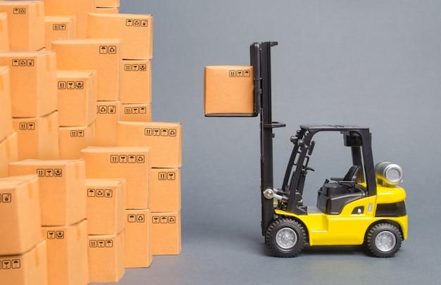Żółty wózek widłowy podnosi pudełko na stosie pudełek. magazynowanie towarów w magazynie