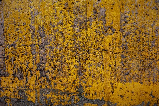 Żółty wzór farby na starej betonowej ścianie, stara żółta farba na ścianie cementowej na abstrakcyjnym tle