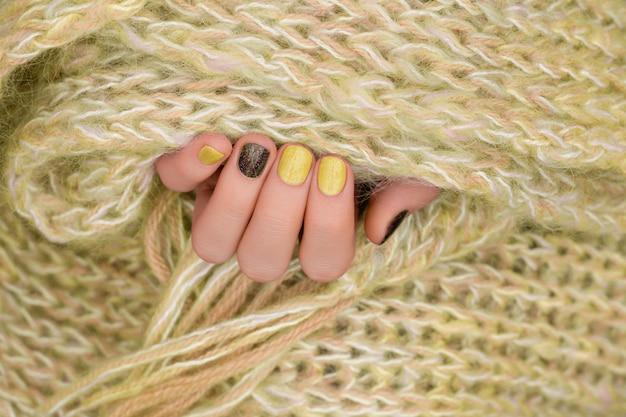 Żółty wzór paznokci. wypielęgnowana ręka z brokatem do manicure.