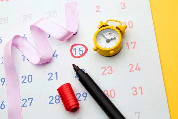 Żółty zegar z czerwonym zakreślaczem ze znakiem dnia owulacji w kalendarzu.