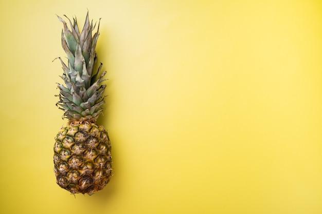 Żółty zestaw ananasów lub ananasów, na żółtym tle z teksturą lato, widok z góry płasko leżący, z miejscem na kopię dla tekstu