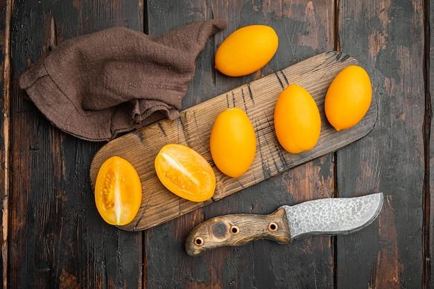 Żółty zestaw pomidorów, na starym ciemnym tle drewnianego stołu, widok z góry płaski lay