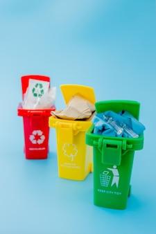 Żółty, zielony i czerwony kosze z symbolem recyklingu na niebieskiej ścianie. utrzymuj porządek w mieście, pozostawia symbol recyklingu. koncepcja ochrony przyrody.