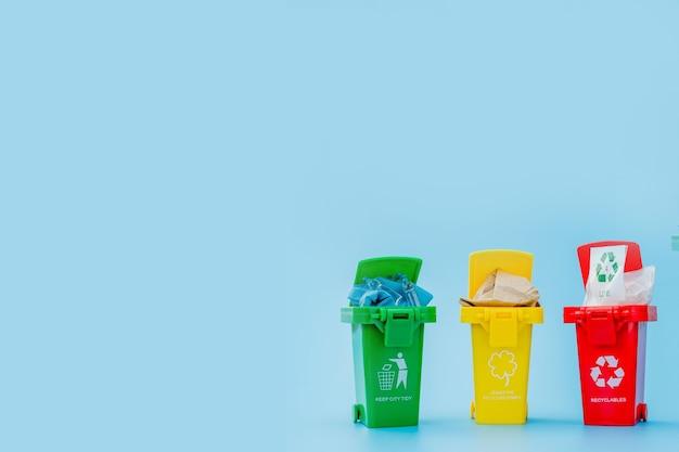 Żółty, zielony i czerwony kosze z symbolem recyklingu na niebieskim tle. utrzymuj porządek w mieście, pozostawia symbol recyklingu. koncepcja ochrony przyrody.