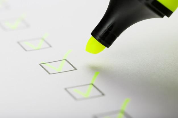 Żółty znacznik ze znacznikami na arkuszu listy kontrolnej. lista kontrolna zakończona koncepcja zadania.
