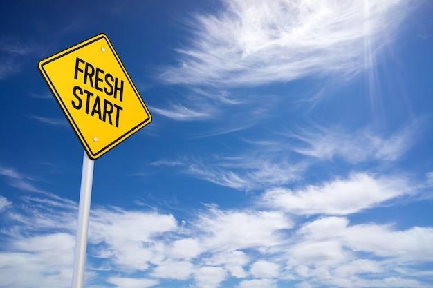 Żółty znak drogowy fresh start z niebieskim tłem nieba