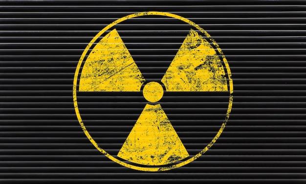 Żółty znak ostrzegawczy zagrożenia radioaktywnego namalowany na tle czarnej metalowej ściany grunge z miejscem na kopię