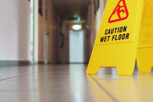 Żółty znak śliskiej podłogi w pokoju po sprzątaniu