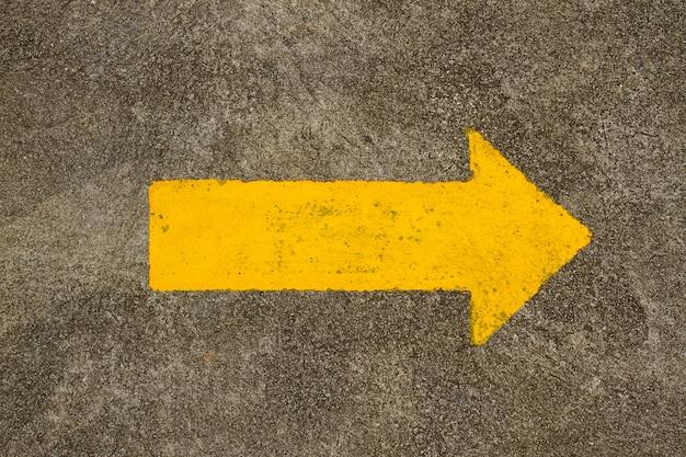Żółty znak strzałki na drodze