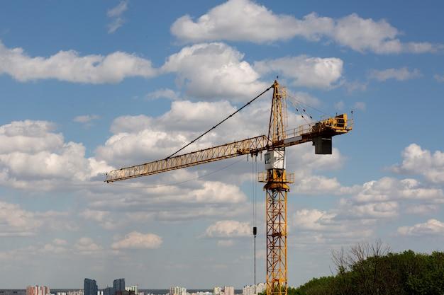 Żółty żuraw wieżowy pracujący na budowie w słoneczny dzień