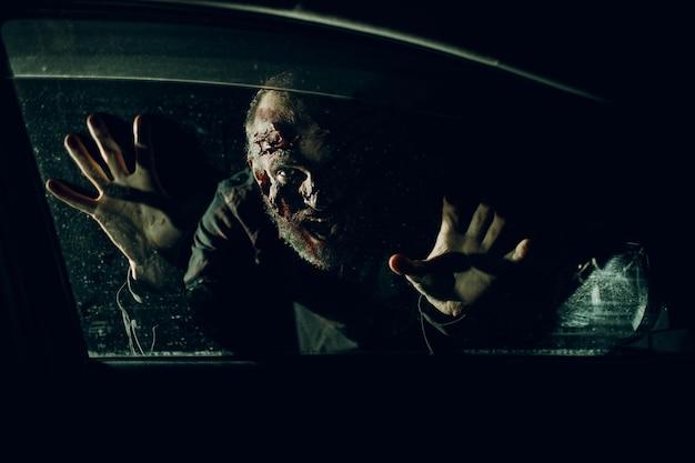 Zombie mężczyzna atak kierowcy samochodu przez koncepcję halloween szyby pojazdu.
