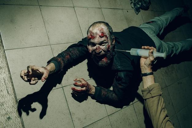 Zombie mężczyzna skrada się na podłodze koncepcja halloween. lekarz ze strzykawką do szczepionki w ręku