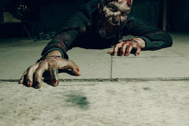 Zombie mężczyzna skrada się na podłodze koncepcja halloween. makijaż skóry i zakrwawionej twarzy