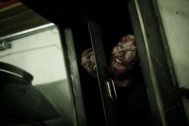Zombie patrząc koncepcja halloween otwarte drzwi. makijaż skóry i zakrwawionej twarzy
