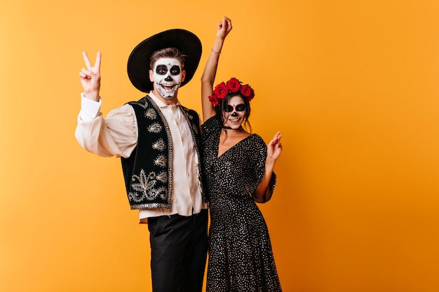 Zombie w meksykańskich strojach wyrażające szczęście. urocza młoda kobieta świętuje halloween z przyjacielem.