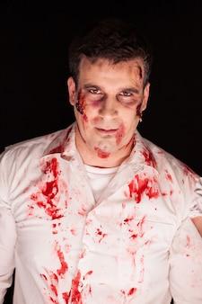 Zombie z krwią na nim po zabójstwie na czarnym tle. upiorny człowiek.