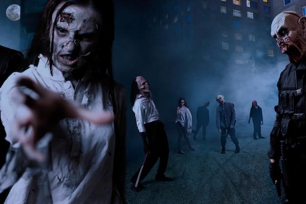 Zombie z zakrwawionymi twarzami na nocnej ulicy w centrum miasta, zabójcza armia potworów. horror w mieście, atak nieumarłych creepy crawly, apokalipsa końca świata
