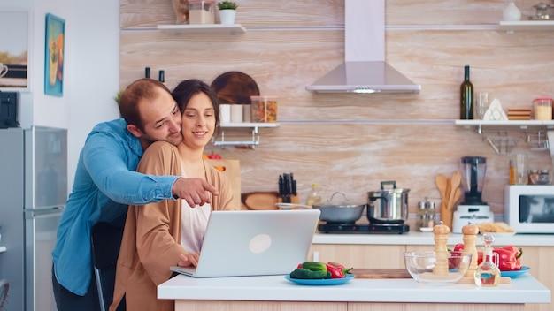 Żona czyta na laptopie w kuchni, podczas gdy mąż ją przytula. mąż i żona gotowanie żywności przepis. szczęśliwy zdrowy styl życia razem. rodzina szukająca posiłku online. zdrowa świeża sałatka