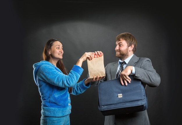 Żona daje mężowi paczkę z przekąskami