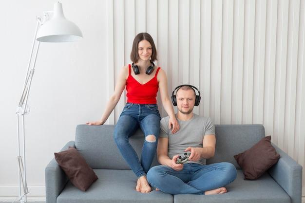 Żona i mąż grają razem w gry wideo w domu