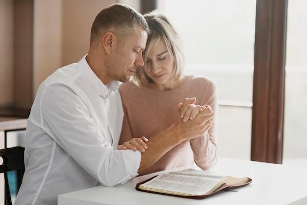 Żona i mąż modlą się razem w domu