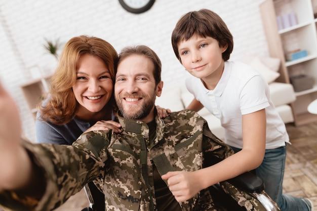 Żona i syn chętnie widzą mężczyznę i robią selfie.