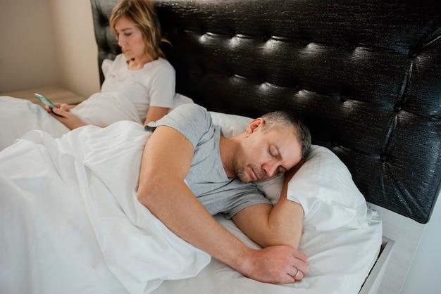 Żona korzystająca z telefonu komórkowego, gdy mąż śpi