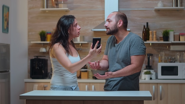 Żona krzyczy na niewiernego męża w kuchni. zazdrosna kobieta zdradzała zła, sfrustrowana, obraziła się, zirytowana, oskarżając swojego mężczyznę o niewierność pokazując mu wiadomości na smartfonie krzycząc zdesperowany.