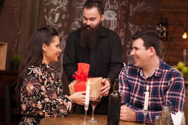Żona odbiera prezent od ukochanego męża. hipsterski pub.