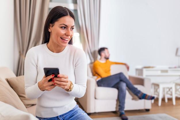 Żona odwróciła się plecami do męża, czytając wiadomość na telefonie od swojego kochanka, mężczyzny leżącego na kanapie z tyłu