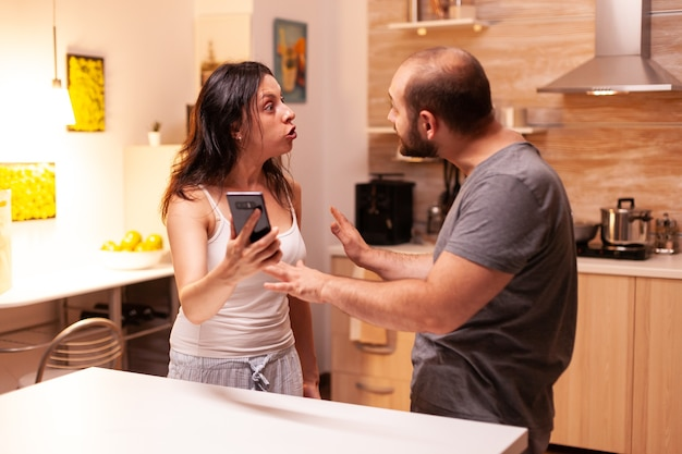 Żona prosi o wyjaśnienie od zdradzającego męża w domowej kuchni, wskazując na telefon. podgrzana zła sfrustrowana obrażony zirytowany oskarżając swojego mężczyznę o niewierność pokazując mu wiadomości.