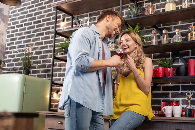 Żona się śmieje. blondynka atrakcyjna stylowa żona śmiejąca się podczas picia wina z mężem