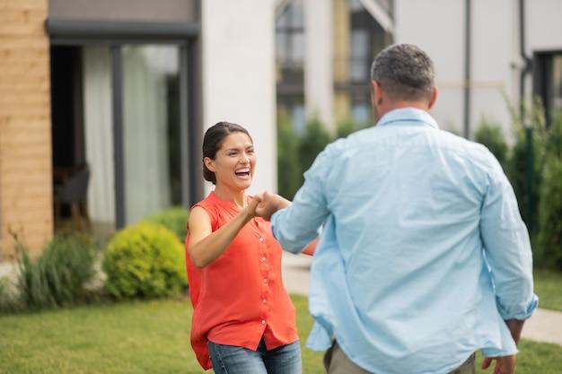 Żona się śmieje. ciemnowłosa piękna żona śmiejąca się podczas tańca z mężem w pobliżu domu