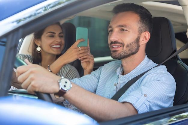Żona się śmieje. żona śmiejąca się podczas robienia zdjęcia brodatemu przystojnemu mężowi prowadzącemu samochód