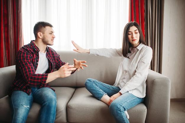 Żona siedzi na kanapie, rozgniewany mąż wrzeszczy na nią