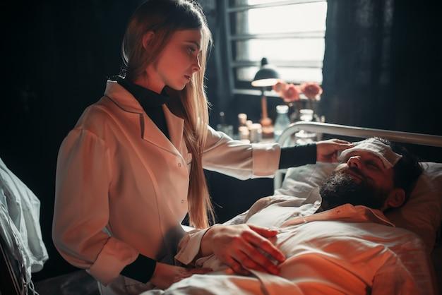 Żona siedzi przed chorym mężem w szpitalnym łóżku
