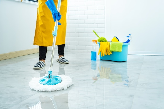 Żona sprzątanie i sprzątanie koncepcja, szczęśliwa młoda kobieta w niebieskie gumowe rękawice do wycierania kurzu za pomocą mopa podczas czyszczenia na podłodze w domu
