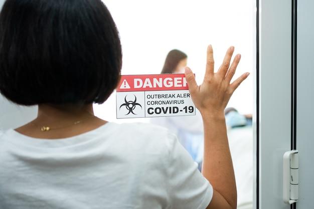 Żona stojąca przed salą kwarantanny i kładąca rękę na lustrze, czekając na wyniki badań