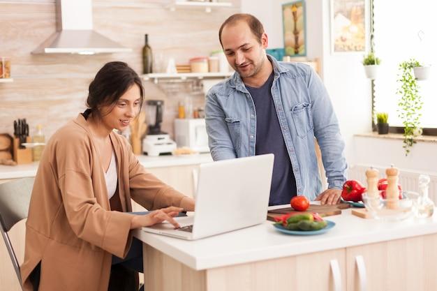 Żona szuka przepisu na sałatkę na laptopie w kuchni razem z mężem. mężczyzna pomaga kobiecie przygotować zdrowy organiczny obiad, wspólne gotowanie. romantyczny, wesoły związek miłosny