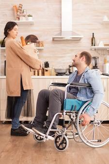 Żona trzyma świeże warzywa w papierowej torbie po mężu niepełnosprawnym na wózku inwalidzkim robi zakupy w supermarkecie. niepełnosprawny sparaliżowany niepełnosprawny mężczyzna z niepełnosprawnością chodzenia integrujący się po wypadku