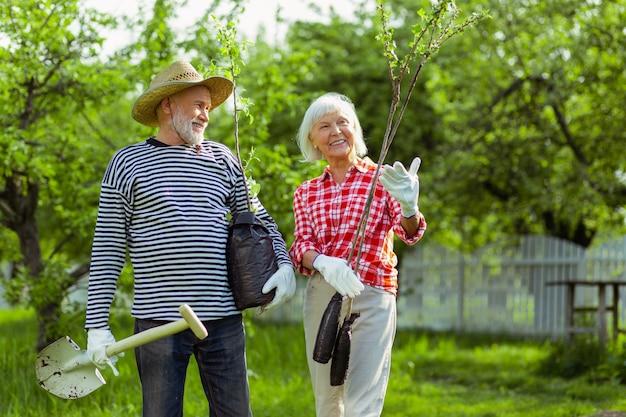 Żona uśmiecha się. kochająca żona uśmiechająca się podczas sadzenia drzew wraz z mężem w pobliżu męża w domku